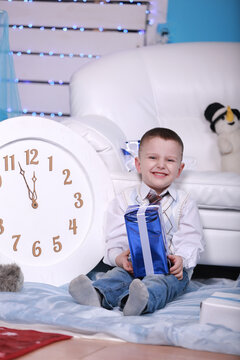 smiling cute boy holding his present during christmas time. big white clock and teddy bear on background