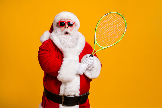 Portrait of his he nice attractive amazed stunned wondered funny Santa enjoying playing badminton team cup contest workout isolated bright vivid shine vibrant yellow color background