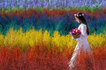 Wall Mural - Beautiful girl in white dress sitting in Cutter rainbow flowers fields, Chiang Mai.