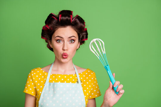Oops. Photo of cute lovely young lady roller hairstyle pouted lips staring hold plastic whisk dough forget turn off microwave wear dotted apron shirt isolated green color background