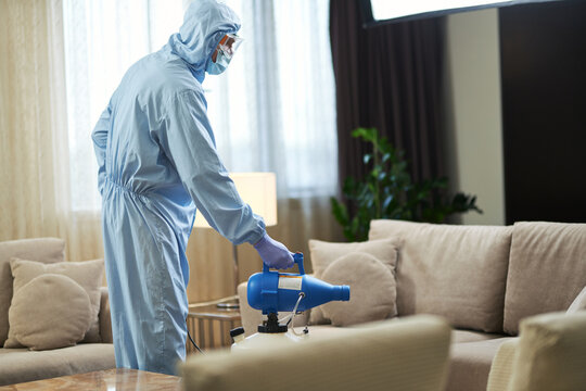 Man standing near the sofa and using disinfectant in hotel room