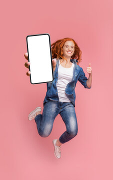 Happy redhead girl jumping with smartphone and showing thumb up