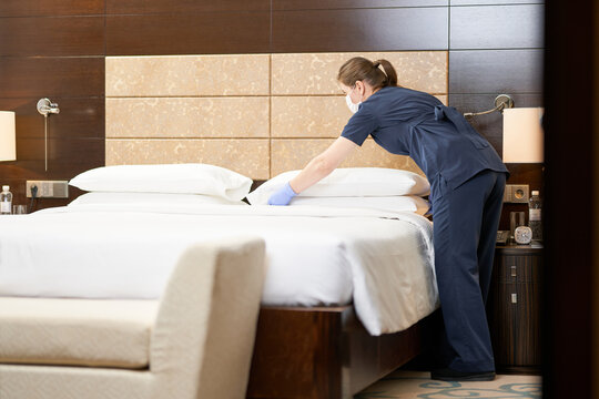 Housemaid standing near bed while cleaning the room in hotel
