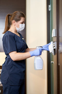 Chambermaid cleaning the hotel room with a disinfectant
