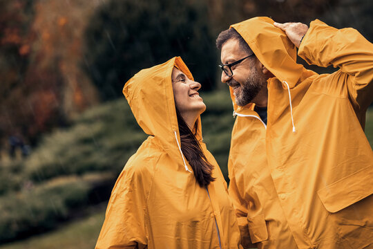 Portrait of mid adult couple in raincoat enjoying together on rain in city park.