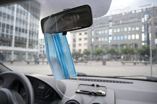Surgical face mask against infection with covid-19 is hanging ready to use on the rear view mirror in a car during the coronavirus pandemic, copy space