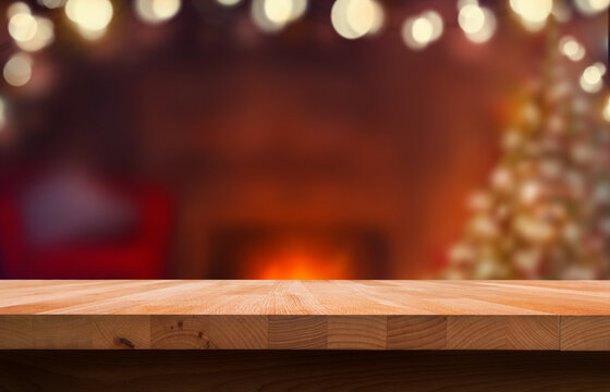 A Christmas wood tabletop product display with a festive background of a Christmas tree and open fire and an empty space on the table.