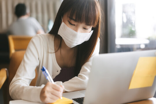 Young adult asian student female with face mask for virus corona or covid 19 study at cafe.