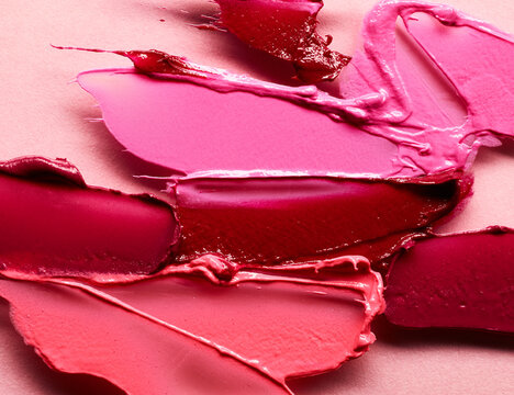 Smudged lipsticks different colors over pink background