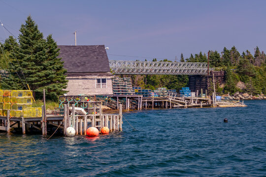 Fishing Shed & Wharf - Shed and wharf full of lobster traps in a small fishing community on the Atlantic Coast of Nova Scotia. Buoys float in the water near the wharf.