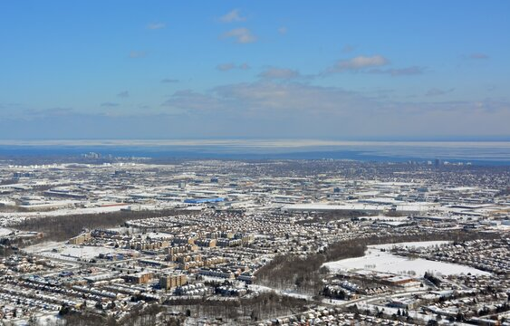 Aerial view across Burlington Ontario,  with Lake Ontario and Oakville in the far background, snow covered
