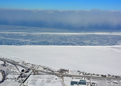 Aerial view along the Queen Elizabeth Way near St Catharines Ontario, Winter scene with view of frozen Lake Ontario
