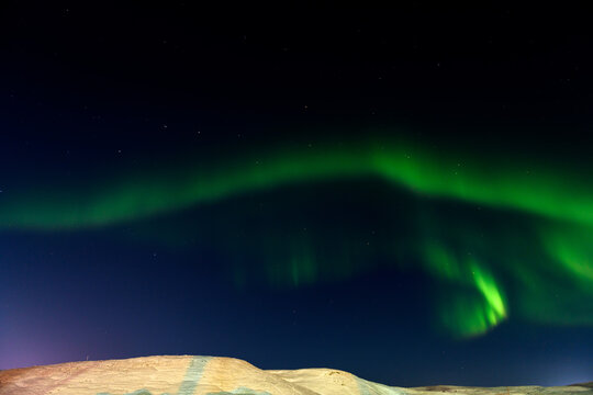 Aurora borealis in winter time. Northern lights. Sky with stars and northern lights and winter landscape.