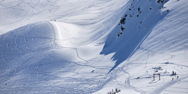 Panoramic view of the snowy mountain slope with ski tracks at Whistler resort in Canada.