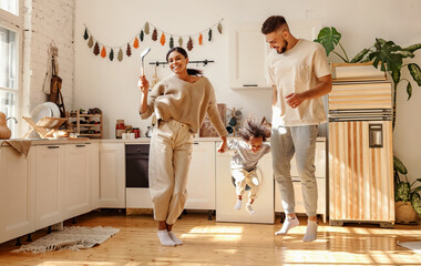 Energetic multiracial family playing and dancing in kitchen.
