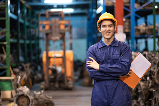 Asia engineer man worker wears a safety helmet and holding tablets. Crossed arm and standing in the automotive spare parts warehouse. Maintainance and service concept. Many old engines