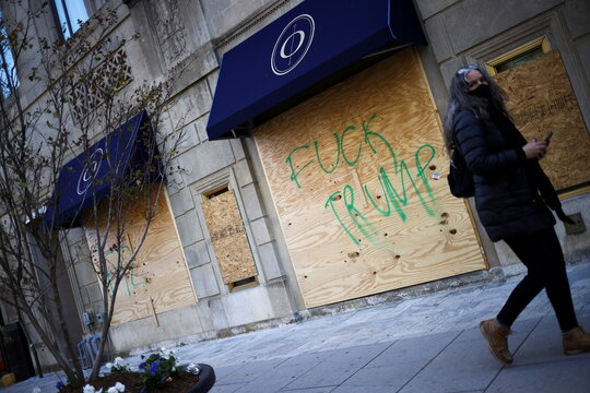 A woman walks in front of a boarded store near the White House