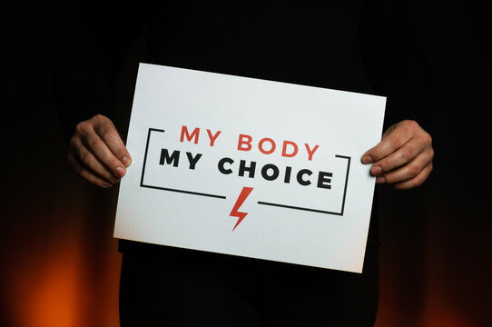 """Woman holding a sign """"My Body, My Choice"""". Protest against tightening of the abortion law in Poland. Nationwide women's strike. Wearing mask against COVID-19 Coronavirus."""