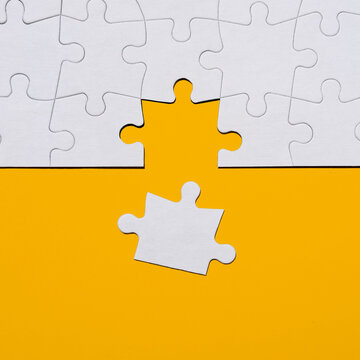 Last puzzle piece in jigsaw puzzle on yellow background