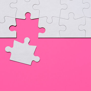 Last puzzle piece in jigsaw puzzle on pink background