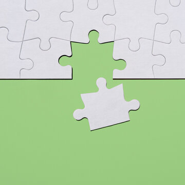 Last puzzle piece in jigsaw puzzle on green background