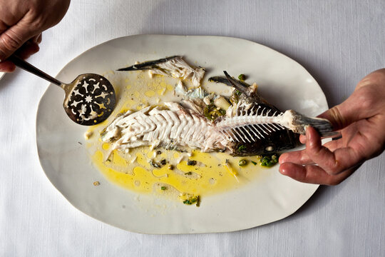 Overhead view of man holding roasted fish with lime salsa verde on plate
