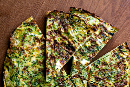 Overhead view of frittata with grated zucchini, goat cheese and dill