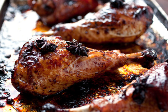 Close up of roasted turkey drumsticks with star anise and soy sauce on baking tray