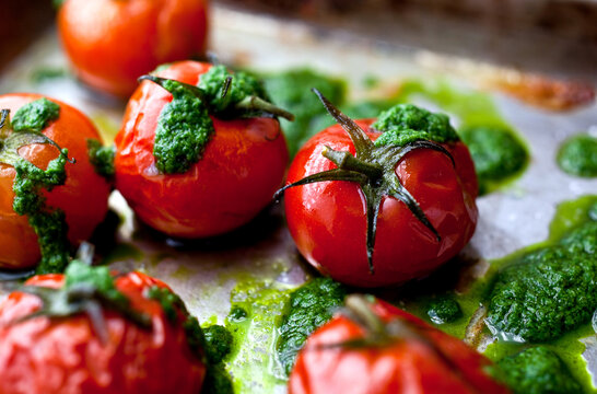 Close up of roasted cherry tomatoes with basil oil in baking tray