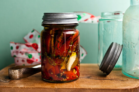 Sweet peppers preserved in oil in glass bottle on table
