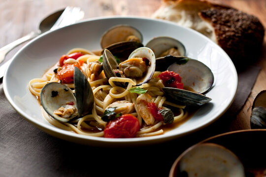 Close up of linguine with littleneck clams and roasted cherry tomatoes served on plate