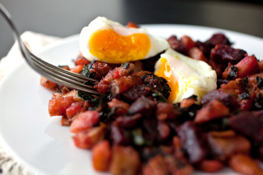 Close up of vegetable hash with poached egg served on plate