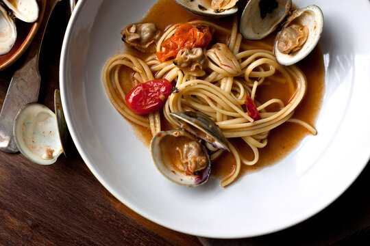 Close up of linguine with littleneck clams and roasted cherry tomato served on plate