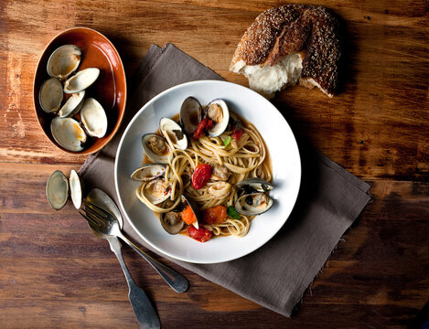 Overhead view of linguine with littleneck clams and roasted cherry tomatoes served on plate