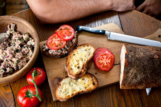High angle view of tuna sandwich with toasted bread and tomatoes on table