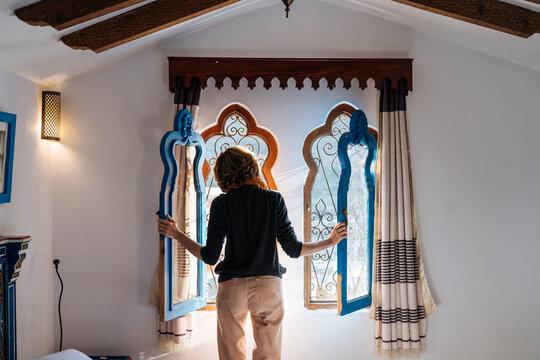 Woman standing by original shaped open window