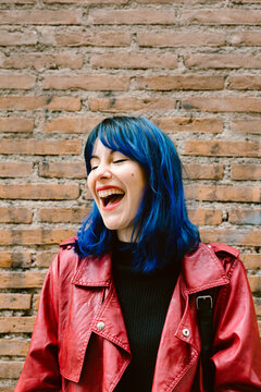 portrait of young woman with blue hair and red lips laughing happy.