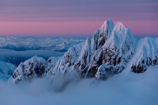Snow covered mountains at sunset from the air