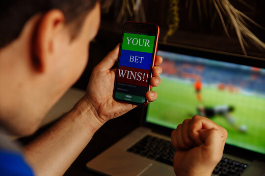 Man being happy winning a bet in online sport gambling application on his mobile phone.