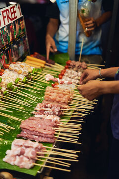 Anonymous travelers buying fresh meat on sticks in market
