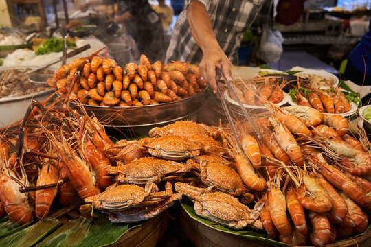 Crop guy taking grilled prawn in street food stall