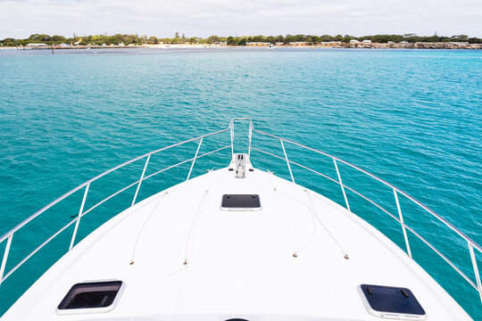 The bow of a luxury yacht sitting in clean clear turquoise ocean waters off the coast of Perth