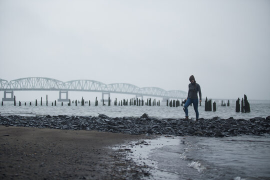 A happy woman walking on a beach beside a long bridge on a foggy day