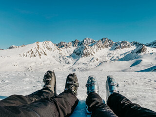 Feet in ski boots in a snowy mountains landscape