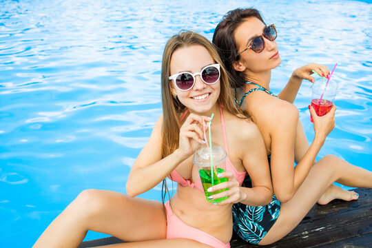 Beautiful and sexy hot tanned girls relaxing near the pool and drinking tropical cocktails. Pretty smilled girls in sunglasses enjoying the summer day and vacation.