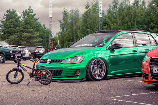 Moscow, Russia - July 06, 2019: Tuned Golf 7 tightened into a green vinyl film. Installed exclusive wheels, air suspension. Lowrider in the parking lot. Side view