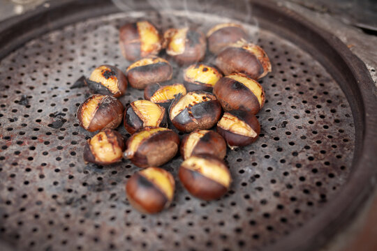 Roasted sweet chestnuts with tongs on counter. Famous traditional Turkish fried chestnuts on the counter of street seller.