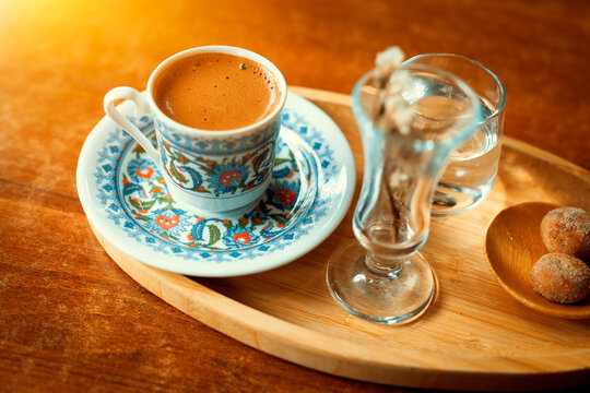 Traditional sparkling turkish coffee served with porcelain cup, cookies, glass of water and flower.