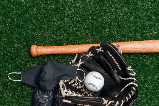 Baseball bat, ball, glove and mask isolated on a field of grass. Baseball season with face mask. Safe sport concept