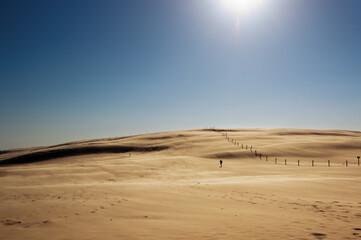 Obraz Krajobraz pustynny błękitne niebo i ruchome piaski  z sylwetką idącego człowieka w pięknym świetle zachodzącego słońca - fototapety do salonu